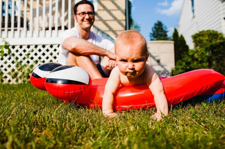 toddler climbs out of red backyard blow up pool, with disgruntled expression, and dad laughing behind him