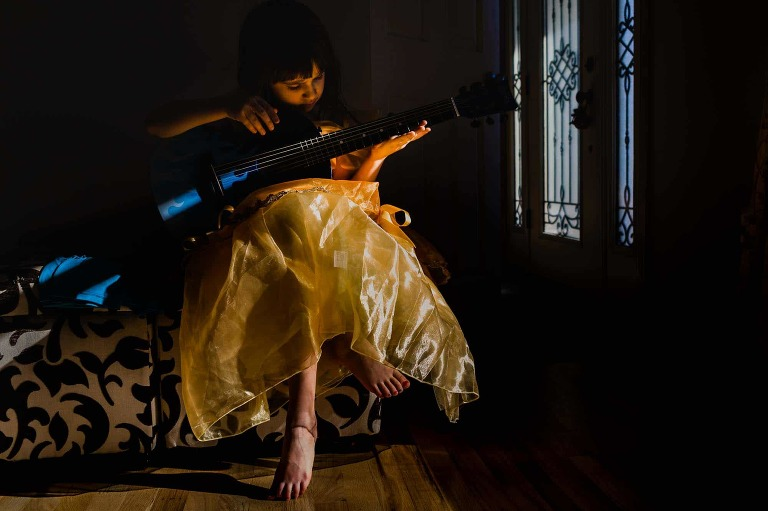 environmental portrait of young girl in princess dress playing guitar, in hard light, with lots of yellow and blue tones
