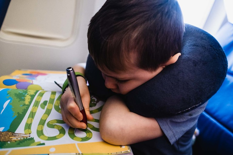little boy on airplane wears sleeping pillow around his neck and does puzzle book