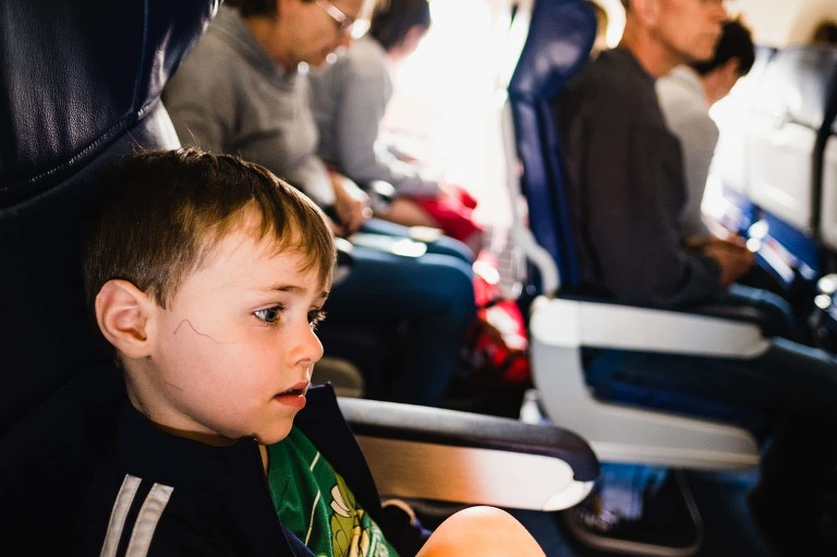 exhausted little boy on the airplane, coming home from disney world. he has writing on his face