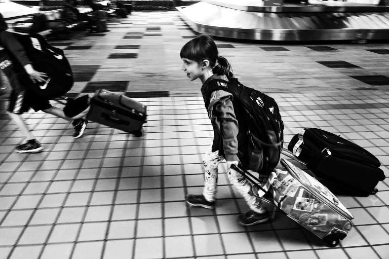 black and white photo of little girl walking through the airport carrying two rolling suitcases and a backpack