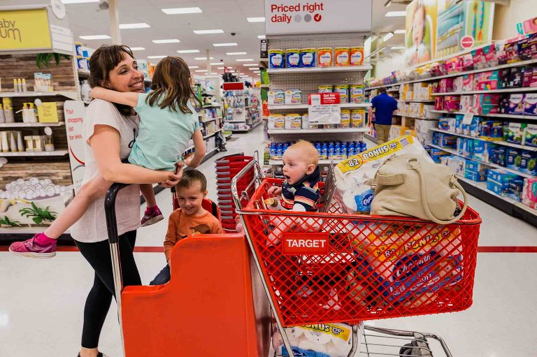 mom takes three young kids through target, riding on the cart