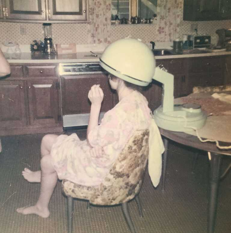 old square photograph of young woman sitting in kitchen chair, dressed in robe, drying her hair using old fashioned hair dryer over her head. woman's face is not visible.
