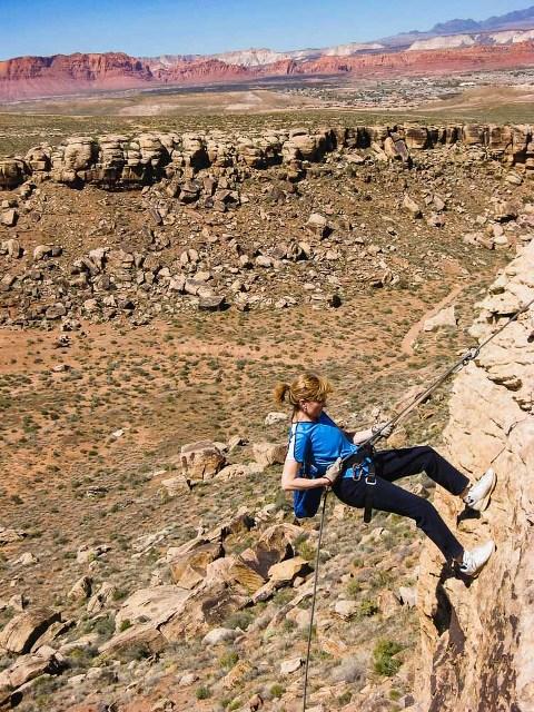 older woman dressed in blue rappelling off a cliff in utah