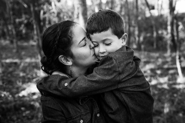 black and white photo of mom kissing her son as she holds him