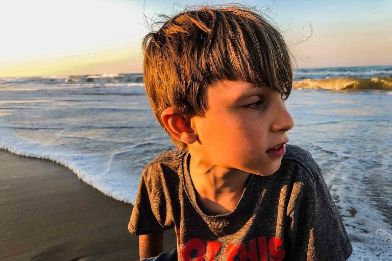 closeup of boy on the beach, looking away from the sun toward the water, medium length hair flying wildly