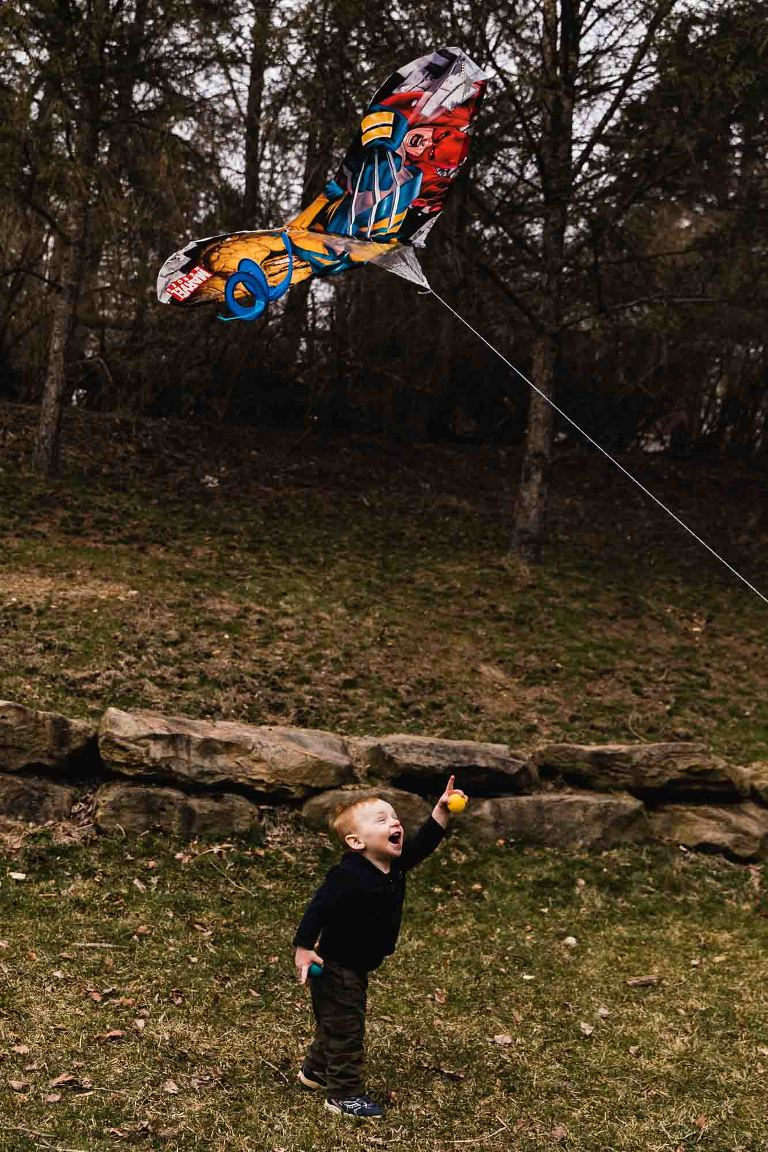 vertical color photo of toddler laughing and pointing up at a kite flying above him, in a mccandless backyard