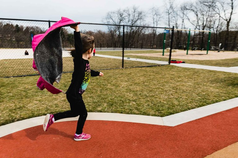 little girl with dark hair, black long sleeve clothes, and pink shoes runs through a playground with her arm in the air clutching her coat flailing in the wind. photograph taken with movement