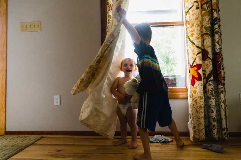 toddler in diaper hides behind curtain as boy pulls curtain away to find him. both boys laughing