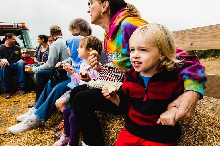 little boy and his family eating apples and riding in a hayride pulled by a tractor