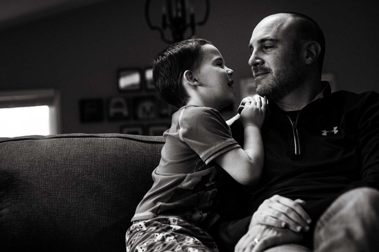 black and white photo of little boy and his dad hanging out on their couch, little boy holding onto his dad's shoulder