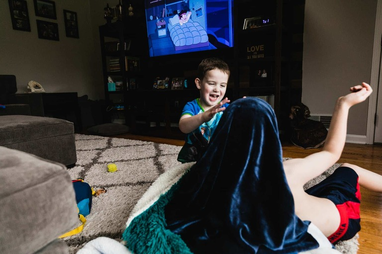 brothers wrestling with a blanket in front of the tv