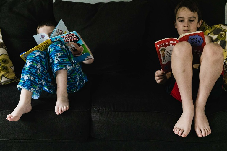 boy and his brothers reading next to each other on the couch, in pajamas