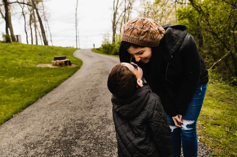 mom leans over to give smiling attention to her young boy