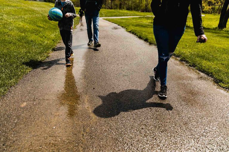 family of four walks together along a path, as photographed below their waists