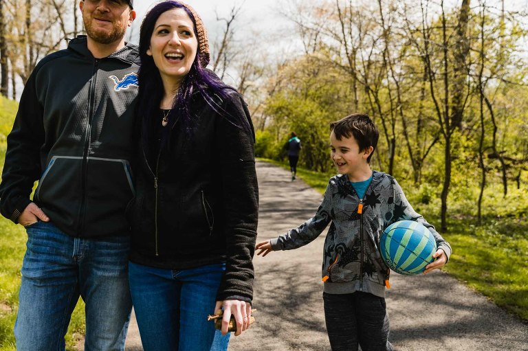 family laughing together on a walk as little boy holding basketball pretends to smack his mom's rear