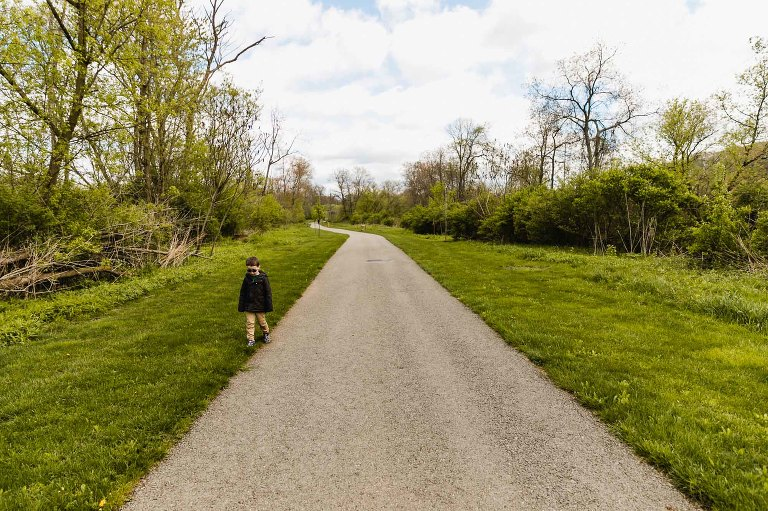 little boy walking outside the path on the grass