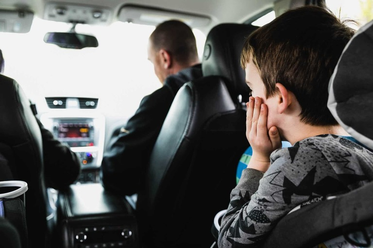 boy in carseat propping his head on his hand as if bored