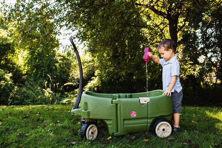 little boy dumping out bubble juice into his wagon, while playing in his backyard