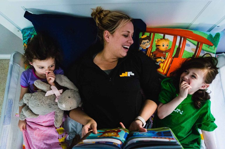 mom lies in bed with two young daughters, reading bedtime stories. laughing with one and the other picks her nose