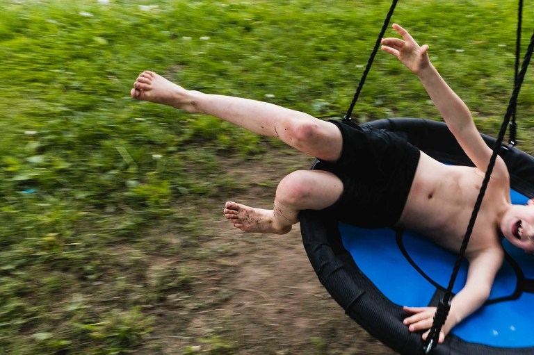 closeup panning action shot of boy swinging on a big disc swing at sunset, legs flailing and dirty bare feet