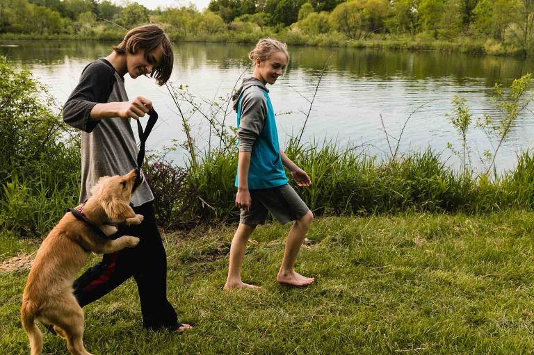 two teenage boys playing with dog in front of lake