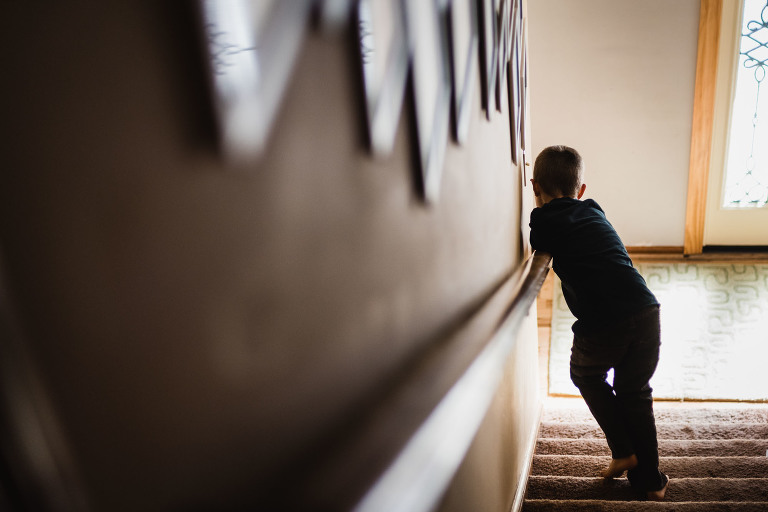 young boy running down the stairs hanging on the railing
