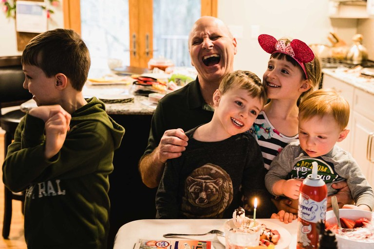 kids singing happy birthday to grandpa at kitchen table