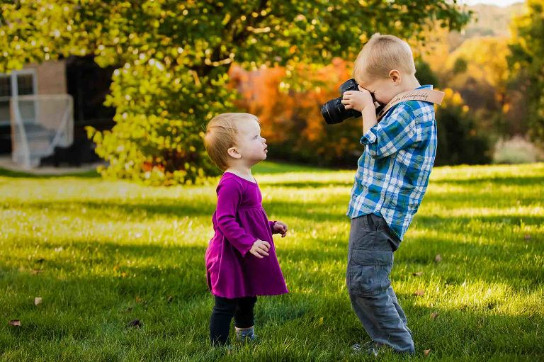 little boy taking picture of little girl with big camera