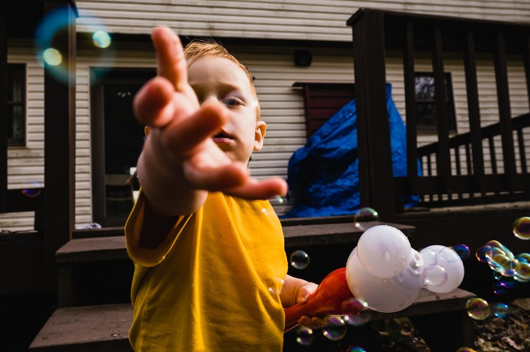 little boy playing with bubbles in the backyard