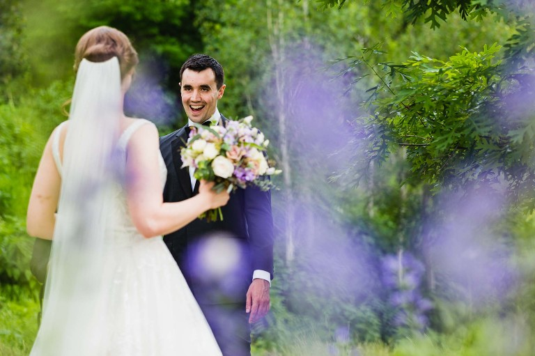groom gives excited look as he sees his bride for the first time on their wedding day
