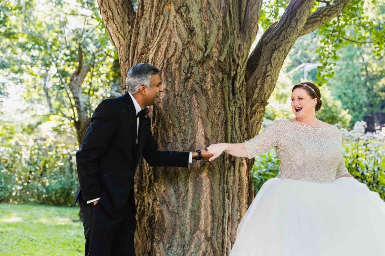 bride and groom holding hands around a tree, seeing each other for the first time on their wedding day