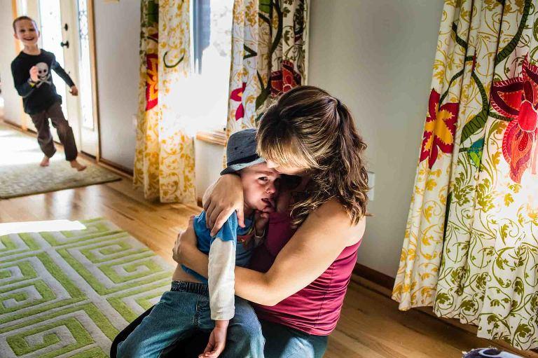 mom cuddling crying boy
