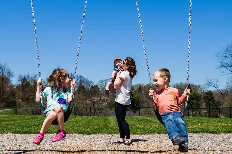 mom kissing baby with kids on swings