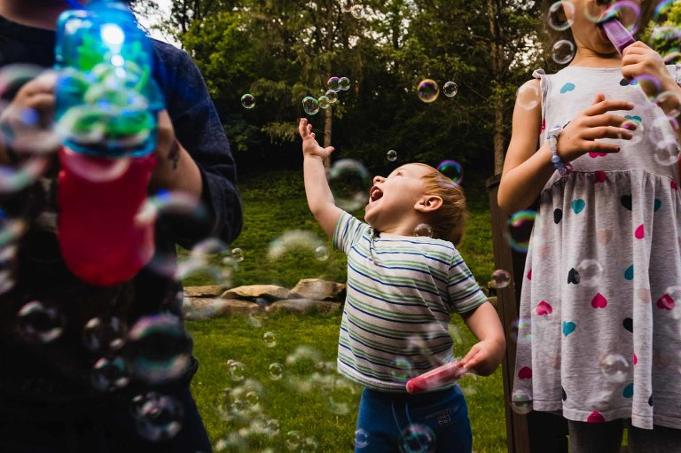 little boy laughing and reaching for bubbles, while his sister is focused on eating a lollipop