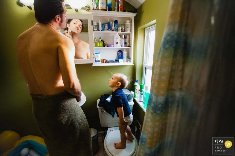 photo of toddler standing on toilet watching dad shave in bathroom