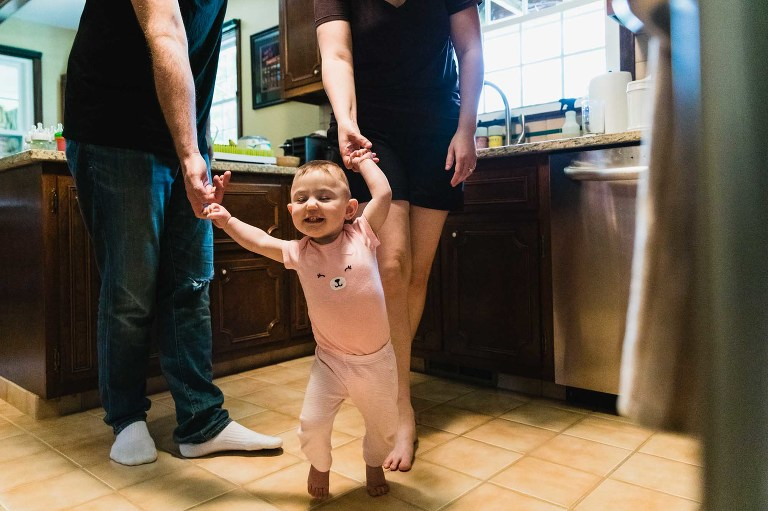 baby learning to walk holds onto mom and dad's hands as she walks through her kitchen