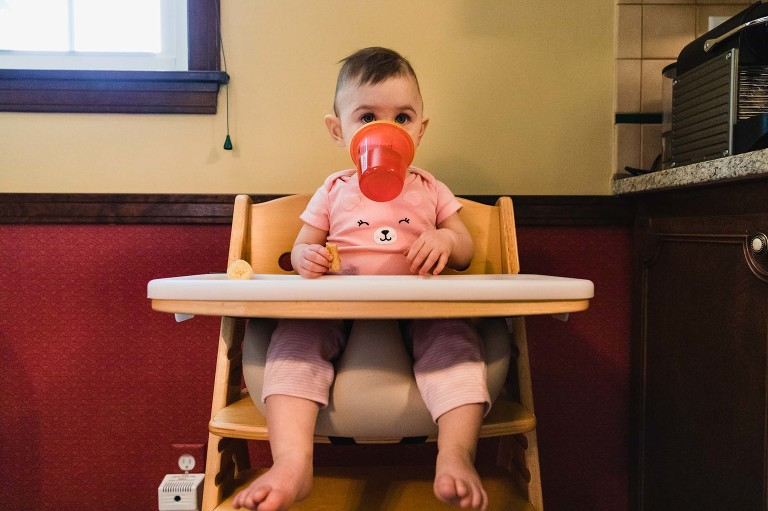 baby sitting in highchair with sippy cup dangling from mouth