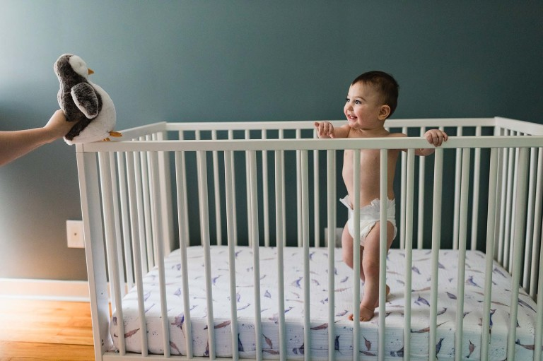 baby playing in her crib by herself, reaching for her favorite stuffed animal penguin that mom is holding out of reach.