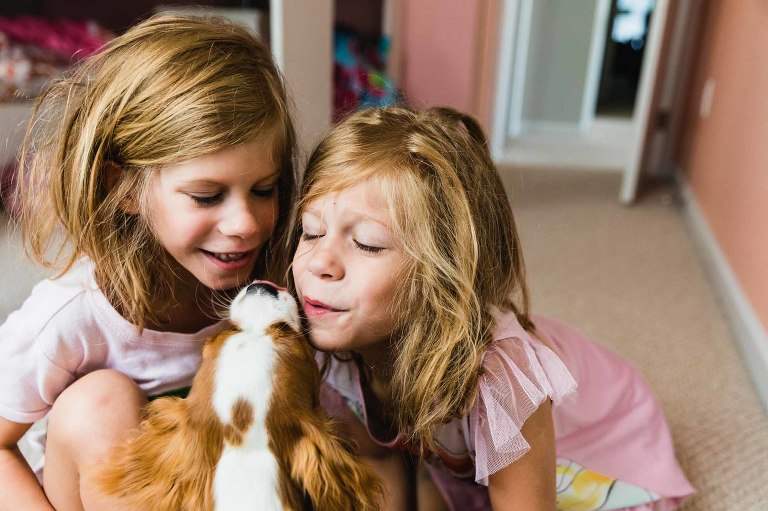 twins with bedhead and pajamas, giving kisses to their puppy on the mouth, in their bedroom.