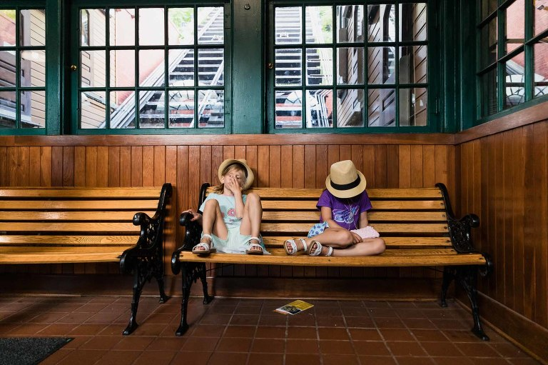 twin girls in hats sit bored on a park bench waiting for the train to arrive