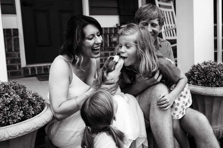 puppy licks little girl's face, surrounded by her family on their front porch.