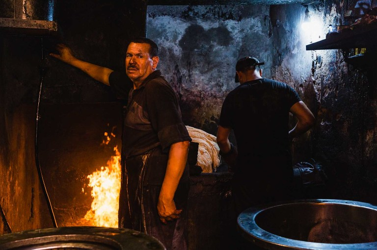 dirty working man in apron leans against a wall in front of a fire