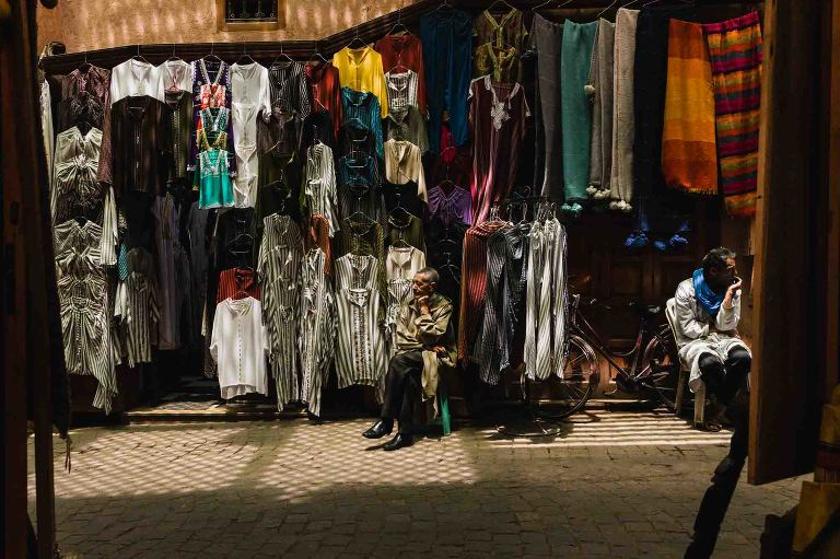 moroccan street vendors sitting in spotty light surrounded by colorful clothes on a narrow street