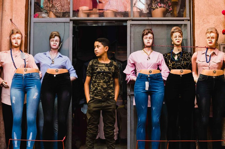 boy stands by creepy mannequins