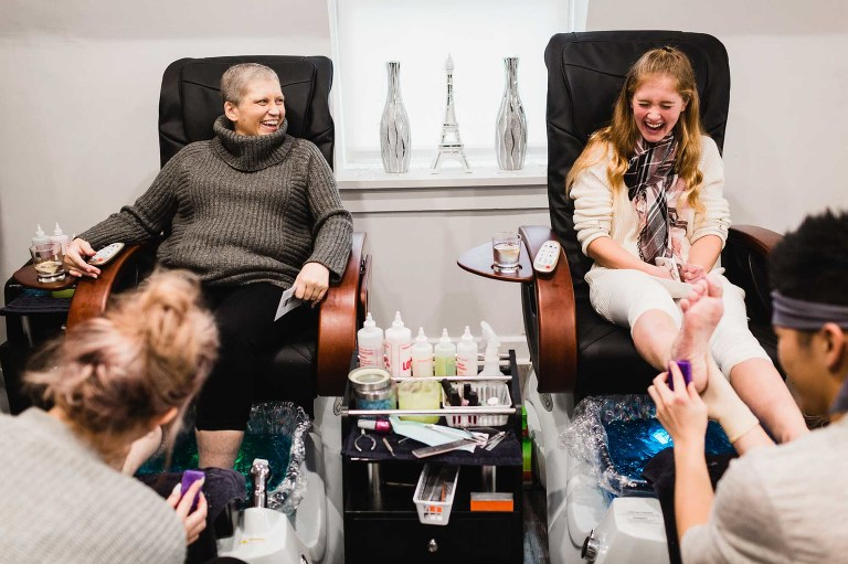 mom and daughter laughing together as they get a pedicure in a nail salon