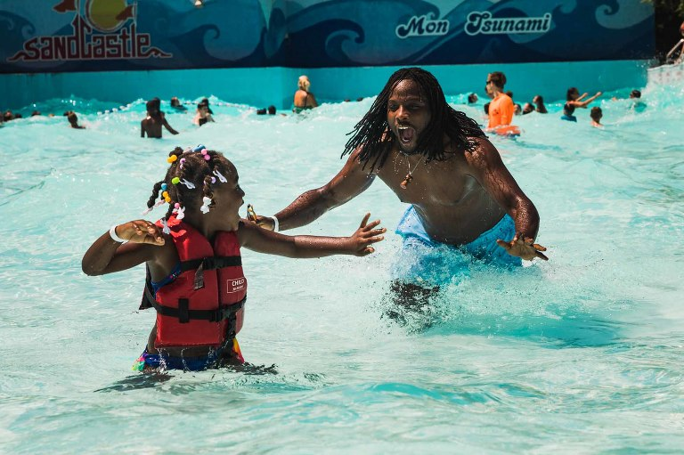african american dad chasing his little girl in wave pool