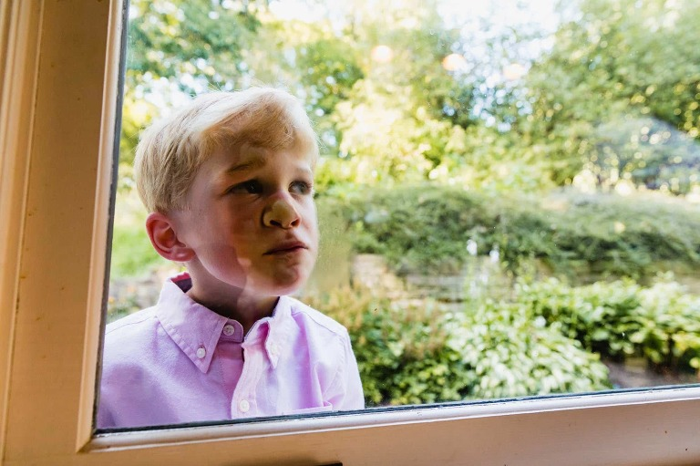 young boy in pink button-down shirt presses his face up against a window, in front of green backyard.