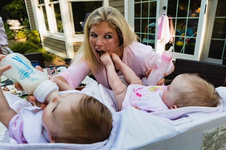 mom feeds twin babies at the same time, while one baby sticks her feet in mom's mouth