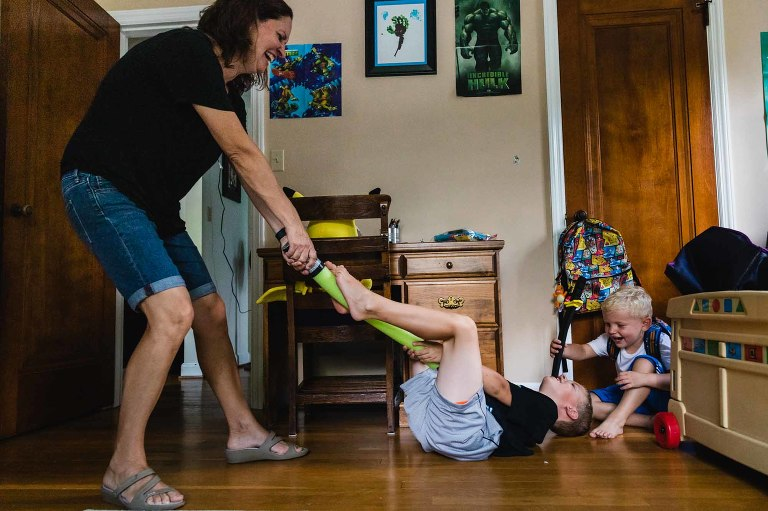mom drags boys across the room by the feet, playing together and laughing